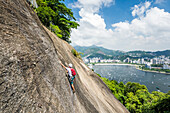Side view of adventurous man rock climbing Morro da Urca next to the Sugarloaf Mountain with city in background, Rio de Janeiro, Brazil