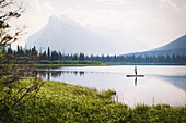 Woman paddleboarding across one of Vermillion Lakes with Mount Rundle in background, Alberta, Canada