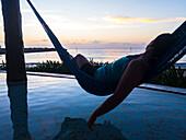 Woman laying in hammock at sunrise and looking out at ocean, Puerto Morelos, Yucatan Peninsula, Mexico