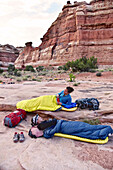 Side view of two women in sleeping bags while camping in Canyonlands National Park, Moab, Utah, USA
