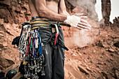 Mid section shot of rock climber applying chalk on hands, Moab, Utah, USA