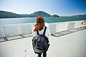 Rear view of woman with backpack standing on ferry deck