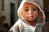 Headshot portrait of baby boy in hooded knit sweater