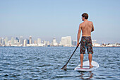 Rear view shot of shirtless stand up paddleboarder against skyline of city of San Diego under clear sky, California, USA