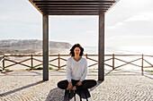 Female yoga practitioner meditating on outdoor bench, Lisbon, Portugal