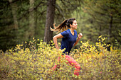 Side view of young athletic woman trail running in forest