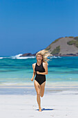 Vacation photo with front view of smiling woman running at beach