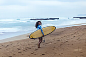 Vacation photo of lone woman carrying surfboard at beach