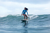 Full length shot of single woman riding wave on surfboard in sea