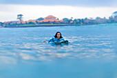 Front view shot of woman paddling on surfboard in sea