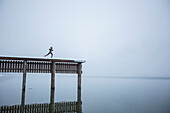 Humorous image of a woman appearing to run off the end of a tall dock into a lake far below. Lake Pend Oreille, Sandpoint, Idaho.