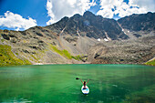 Aerial view of young female sitting on paddle board on high alpine lake in Aspen, Colorado, USA