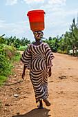 Rear view of African woman carrying bucket on head, Kigali, Rwanda