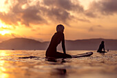 Side view of female surfer in wetsuit in sea at sunset