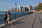 tourists and new yorkers admiring the view of the manhattan skyline and the bay of new york from the promenade on governors island, the hills, governors island, new york city, new york, united states, usa