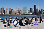 yoga class in gantry plaza state park on the east river across from the skyline of midtown and the headquarters of the un, united nations organization, chrysler building, gantry plaza state park, queens, manhattan, new york city, new york, united states,