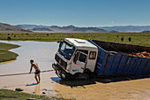 driver trying to get his stuck truck out of a river, altai, bayan-olgii province, mongolia