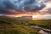 hiker on a verdant stretch contemplating a colorful sunset in front of the high sea cliffs, eidi, eysturoy, faroe islands, denmark