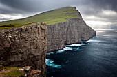 hiker on the edge of the immense cliffs, agitated sea and threatening sky, sorvagsvatn, leitisvatn, vagar, faroe islands, denmark