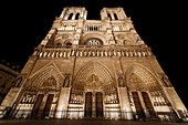 Paris. 4th arrondissement. Cathedral Notre Dame by night. Detail of the facade and gate of the Judgment.