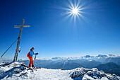 Woman backcountry-skiing standing at summit of Zwiesel, Zwiesel, Chiemgau Alps, Chiemgau, Upper Bavaria, Bavaria, Germany