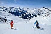 Man and woman backcountry-skiing descending from Rastkogel, Rastkogel, Tuxer Alps, Tyrol, Austria