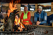 Burning logs in open fire, man and woman out of focus in background, ski arena Kaltenbach, valley of Zillertal, Tuxer Alps, Tyrol, Austria