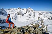 Woman backcountry-skiing looking towards Zwoelferkogel, Steintalspitze, Sellrain, Stubai Alps, Tyrol, Austria