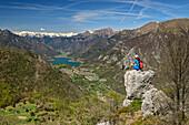 Woman hiking sitting on rock and looking towards lake Tenno and Adamello Group, lake Garda, Garda Mountains, Trentino, Italy