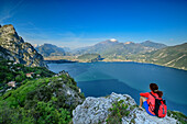 Woman hiking sitting at rock and looking towards lake Garda and Garda Mountains, lake Garda, Garda Mountains, Trentino, Italy