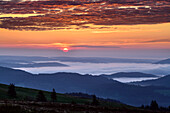 Sunrise at Feldberg with fog in the valley and red glowing clouds, Feldberg, Black Forest, Baden-Wuerttemberg, Germany
