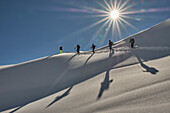 five ski climbers on touring ski in a deep powder slope in the Allgaeu mountains