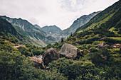 Boulders in the middle of the mountain valley with climbers in the background, E5, Alpenüberquerung, 4th stage, Skihütte Zams,Pitztal,Lacheralm, Wenns, Gletscherstube, Zams to  Braunschweiger Hütte, tyrol, austria, Alps