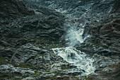 Waterfall in the rock massif with climber on the ascent, E5, Alpenüberquerung, 4th stage, Skihütte Zams,Pitztal,Lacheralm, Wenns, Gletscherstube, Zams to  Braunschweiger Hütte, tyrol, austria, Alps