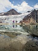 Hiker wanders at a mountain lake with the Pitztal Glacier in the background, E5, Alpenüberquerung, 4th stage, Skihütte Zams,Pitztal,Lacheralm, Wenns, Gletscherstube, Zams to  Braunschweiger Hütte, tyrol, austria, Alps