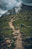 Long distance hiking trail with foggy peaks in the background, E5,Alpenüberquerung,5th stage, Braunschweiger Hütte,Ötztal, Rettenbachferner, Tiefenbachferner, Panoramaweg to Vent, tyrol, austria, Alps