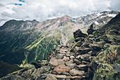 Rocky long distance hiking path with mountain range in the background,Alpenüberquerung,5th stage, Braunschweiger Hütte,Ötztal, Rettenbachferner, Tiefenbachferner, Panoramaweg to Vent, tyrol, austria, Alps