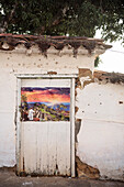 corny poster with Jesus watching sunet at Machu Picchu attached to colonial building, Barichara, Departmento Santander, Colombia, Southamerica