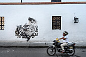 man using mobile phone on motorbike while passing face mural at wall of colonial building, Popayan, Departmento de Cauca, Colombia, Southamerica