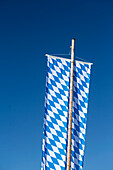 Large Bayer flag with a white-and-blue diamond pattern is a function of the wooden flagpole against blue sky
