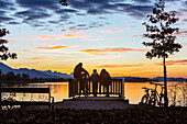 Group of young cyclists in the last evening light on the viewing platform on the Chiemsee in field