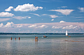 Bathing in glorious summer weather; swimmers and boats on Lake Chiemsee cavort under white-and-blue sky