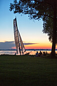 Catamaran is located in the last evening light at the Chiemsee shore, sitting in front of three teenagers under a tree