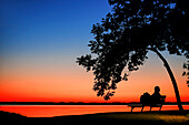 Woman sitting under a tree on a park bench with colorful sunset on Lake Chiemsee