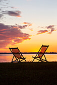 Two deck chairs in the last evening light at the Chiemsee beach at Feldwies