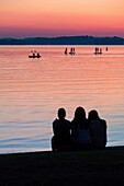 A group of three girls watching standup paddlers and KAYAKERS on the Chiemsee in the sunset