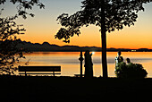 In the last evening light veiled woman makes a cell phone photo of your children on the banks of Lake Chiemsee