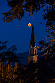Blood Red Moon at the height of the lunar eclipse 2018; in the foreground the parish church of St. Nicholas in overseas behind a corn field