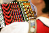 Woman in the bavarian Dirndl plays the diatonic Ziach; view over the shoulder on the decorated bellows of the harmonica