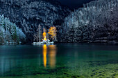The small island in the Lake Königssee with illuminated John Christian Lieger statue in winter mountain scenery